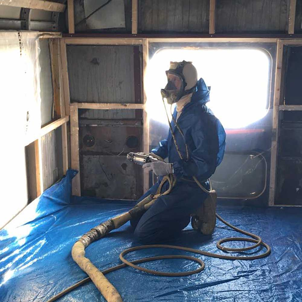 A man in a protective suit and mask holding a spray foam insulation hose