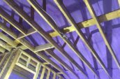 looking up at wooden framing and purple spray foam insulation inside house