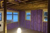 purple spray foam insulation applied to walls of cabin between wooden framing
