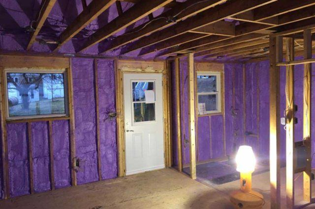 purple spray foam insulation applied to walls of cabin between wooden framing
