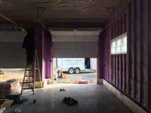 purple spray foam insulation in progress within garage