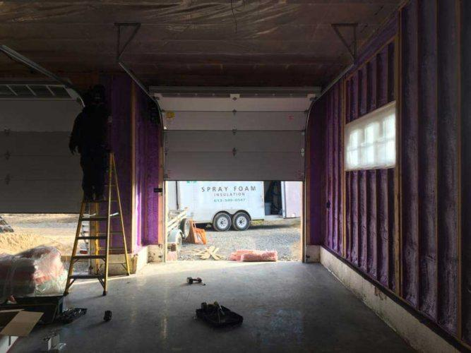 purple spray foam insulation in progress within garage
