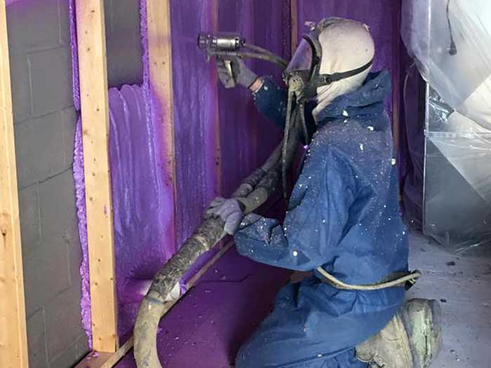 man in blue suit with gas mask applying purple spray foam to wall