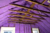 purple spray foam insulation applied on walls and roof between wooden beams