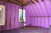 purple spray foam insulation covering walls and roof of farm house