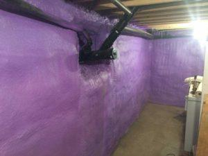 purple spray foam applied around pipes on basement walls