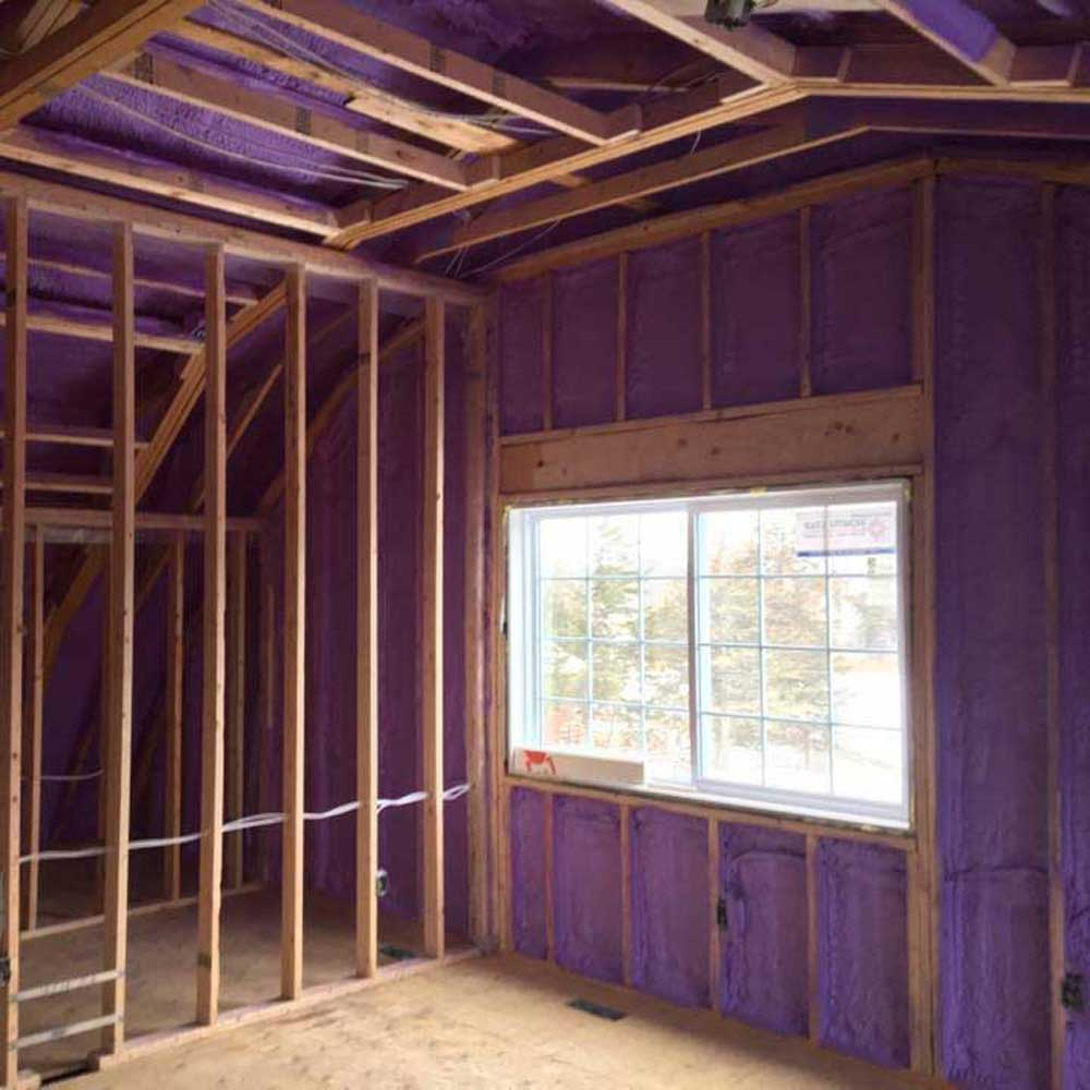 Purple spray foam insulation on the framed walls of a building interior