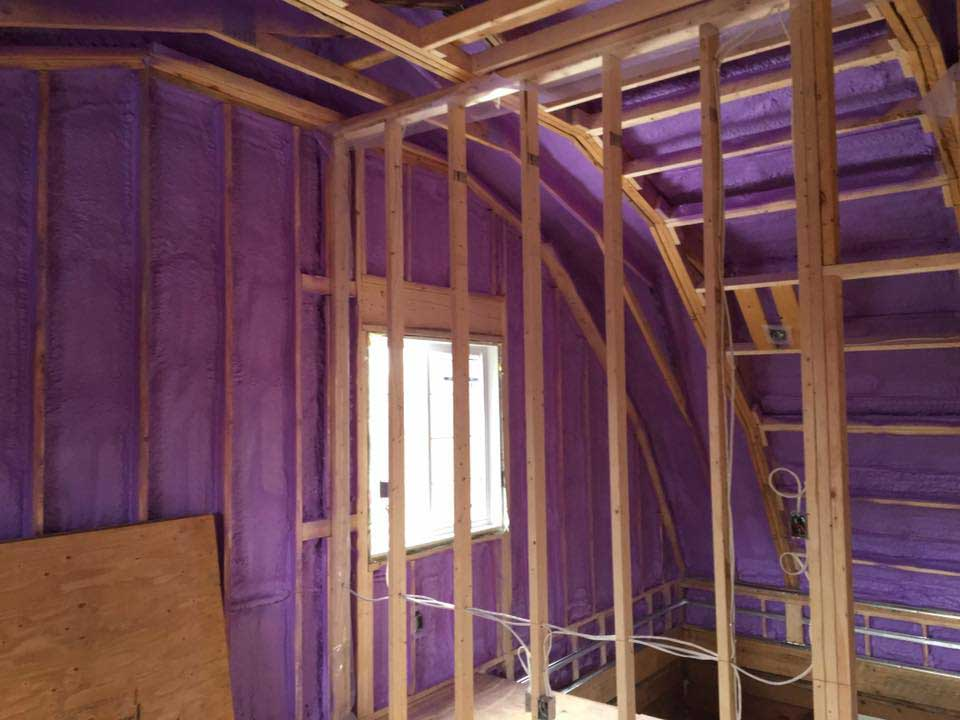 purple spray foam insulation covering walls and roof of house
