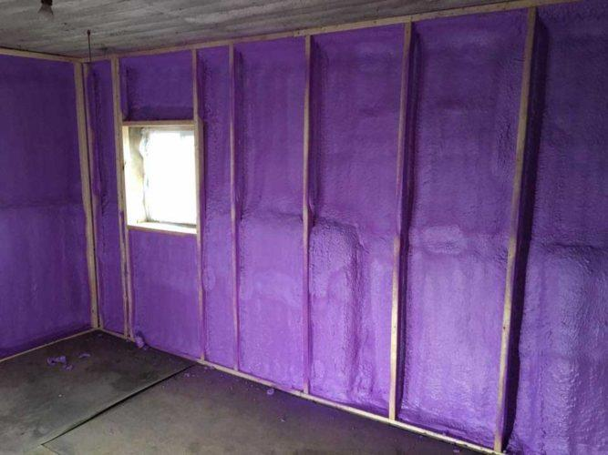 Purple spray foam insulation on the framed walls of an old outbuilding